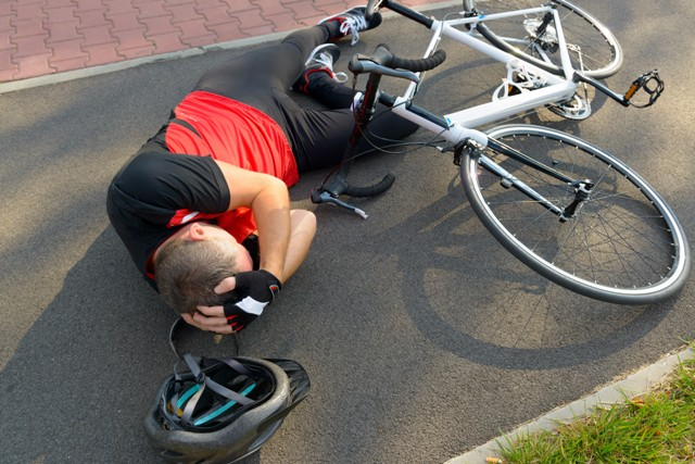 Bicycler on the ground holding his head with his hands